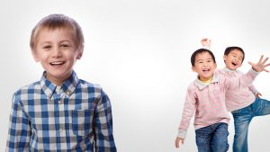 Young Boy Smiling and Two Twin Boys Laughing, Wearing Identical Outfits