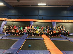 Large Group of Young People Sitting in a Big Trampoline Park